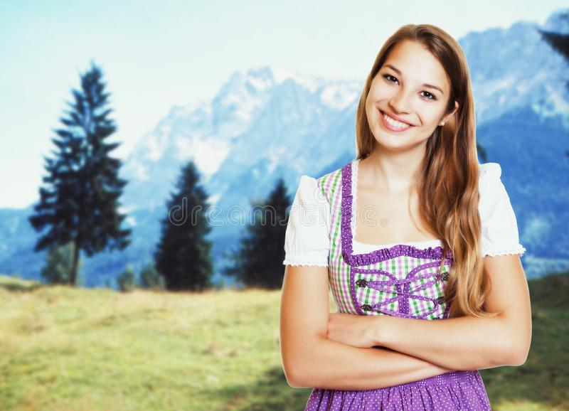 Laughing german woman in bavarian dirndl with rural landscape. In the background stock photo