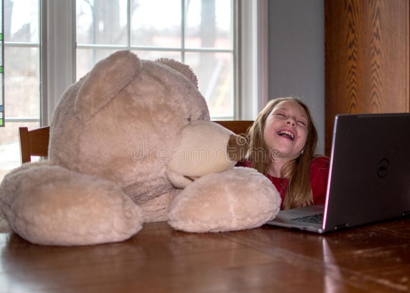 Laughing girl with bear on laptop. Laughing girl watches funny videos with a bear on her lap top stock image