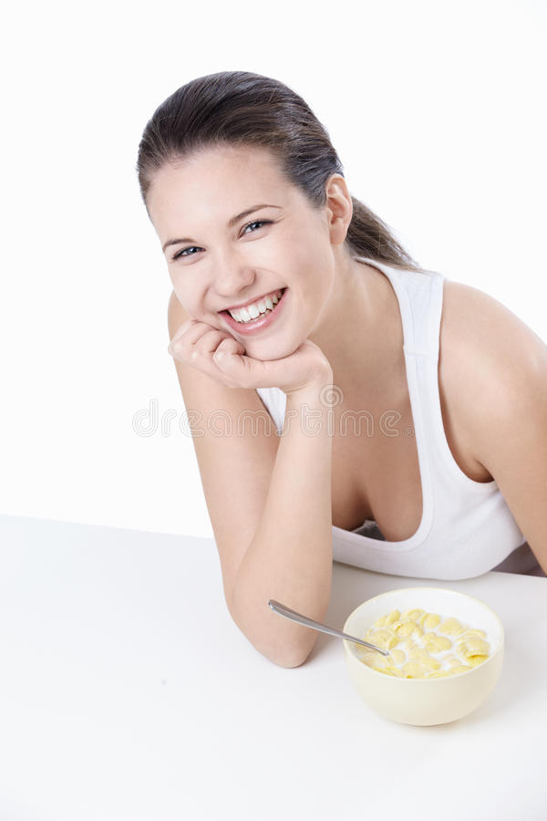 Laughing girl with a bowl of cereal royalty free stock images