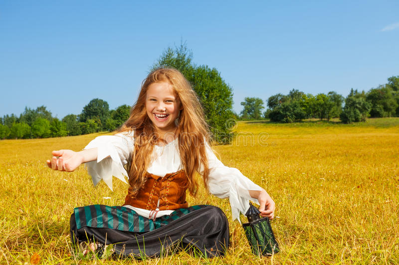 Laughing girl in costume of pirate sitting royalty free stock photography