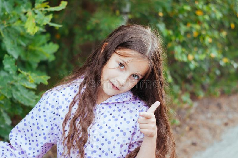 Laughing girl with daisy in her hairs, showing thumbs up stock photo