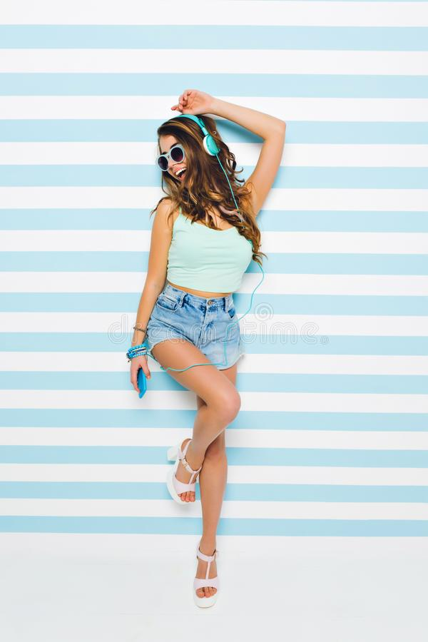 Laughing girl in elegant heeled sandals and stylish sunglasses standing on one leg posing on striped background royalty free stock photography