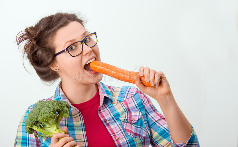 Laughing girl with glasses and broccoli and carrot in the hands royalty free stock photography