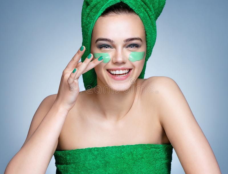 Download Laughing Girl In Green Towels Applying Moisturizing Cream On Her Face Stock Photo - Image of cream, applying: 117257366