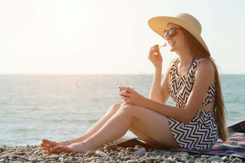 Laughing girl in hat eating ice cream on the beach. sunny day royalty free stock image