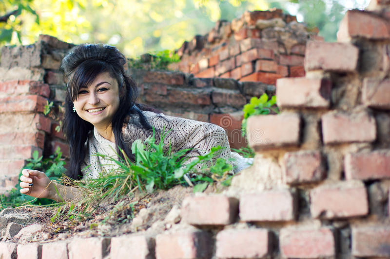 Laughing girl looks out of brick wall royalty free stock images