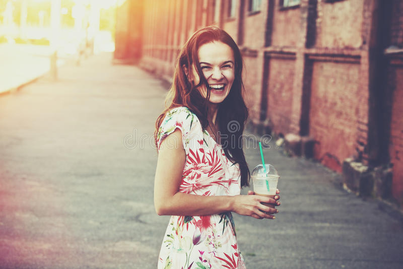 Laughing girl with milk shake. Pretty laughing girl with milk shake walking at morning street royalty free stock images
