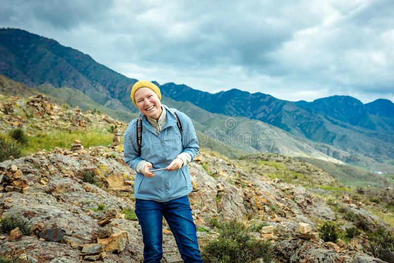 Laughing girl with a mobile in her hand against the backdrop of the mountain landscape. Happy woman traveler in the Altai. Mountains royalty free stock photos