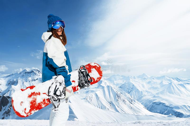 Laughing girl outfit a snowboarder on a background of peaks alpine mountains royalty free stock photography