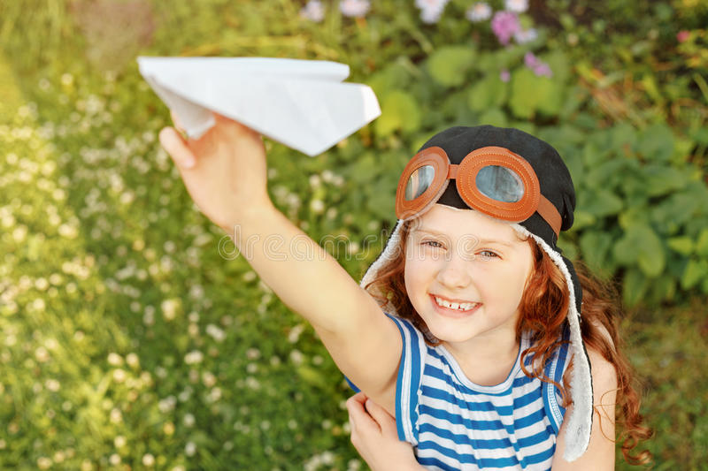 Laughing girl playing with paper airplane. Vacation, freedom concept royalty free stock images