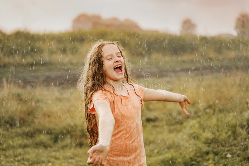 Laughing child spread its arms and catches raindrops. Freedom, happy childhood, healthy lifestyle concept royalty free stock photo