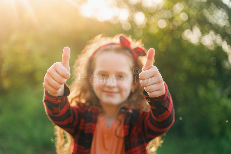 Laughing girl  showing thumbs up stock photo