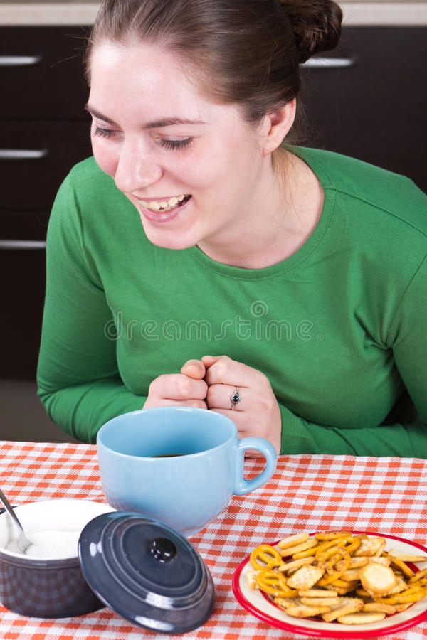 Laughing girl sitting at the table royalty free stock photography