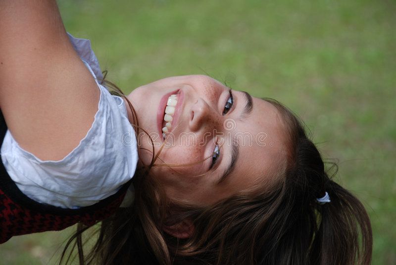 Laughing Girl in a Swing. Beautiful schoolgirl luaghing as she twirls in a swing royalty free stock image