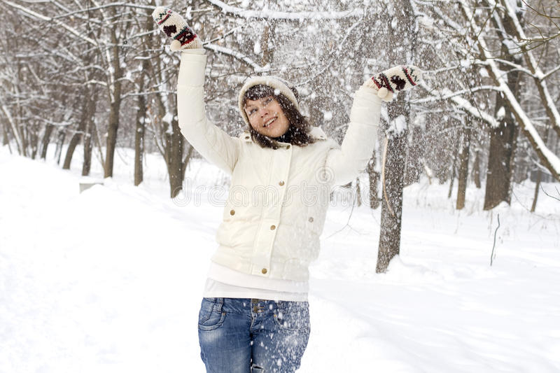 Laughing girl throwing snow royalty free stock images