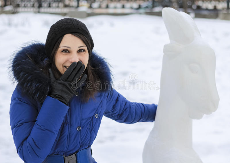Laughing girl in warm coat and a goat in winter, Moscow royalty free stock image