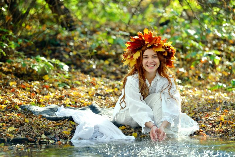 Laughing girl in a wreath from yellow leaves, in a white dress, sitting and playing with the spray of the water stock images