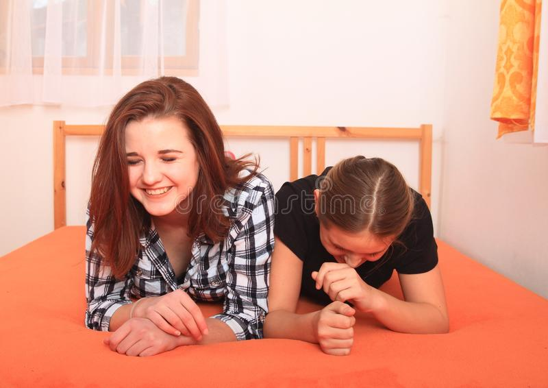 Laughing girls lying on bed stock photos