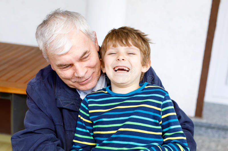 Laughing grandfather with his grandson as they play together. royalty free stock images
