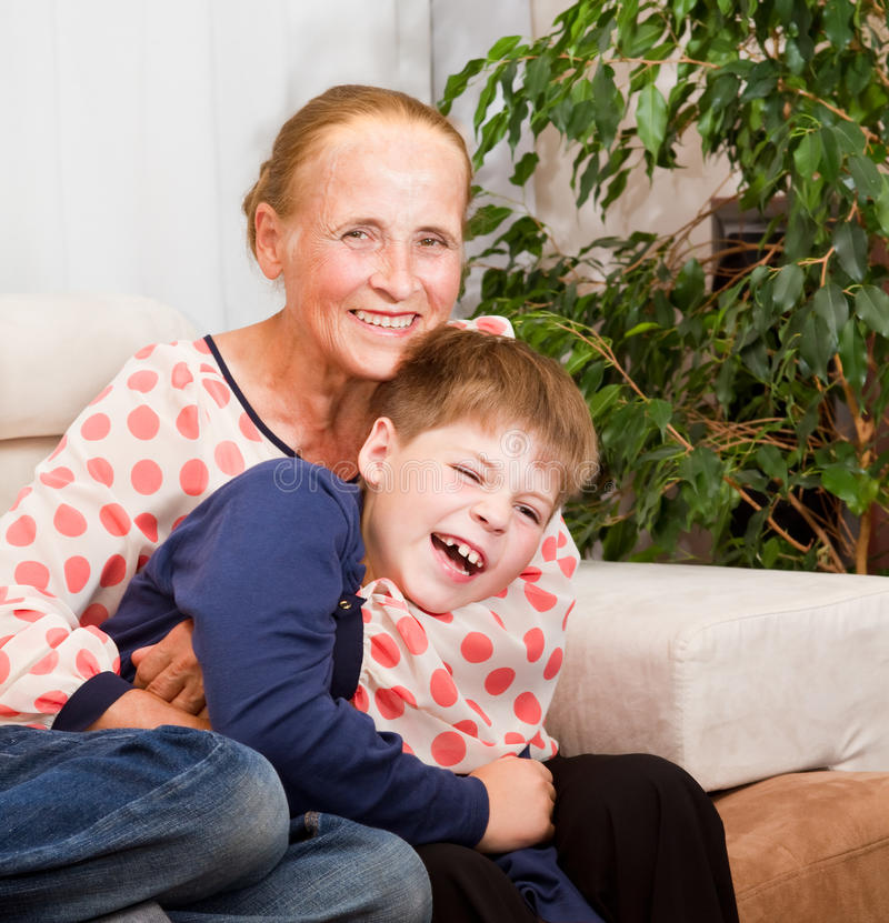 Laughing grandson hugs with grandmother stock photos