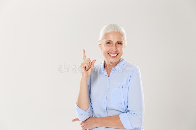 Laughing gray-haired old lady in blue shirt, pointing with finger upward royalty free stock photography
