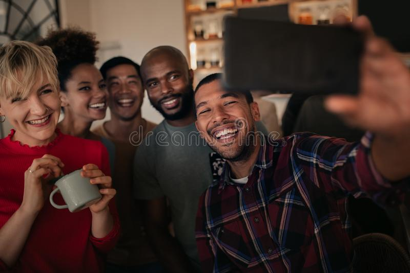 Laughing group of friends taking selfies together in a bar royalty free stock photos