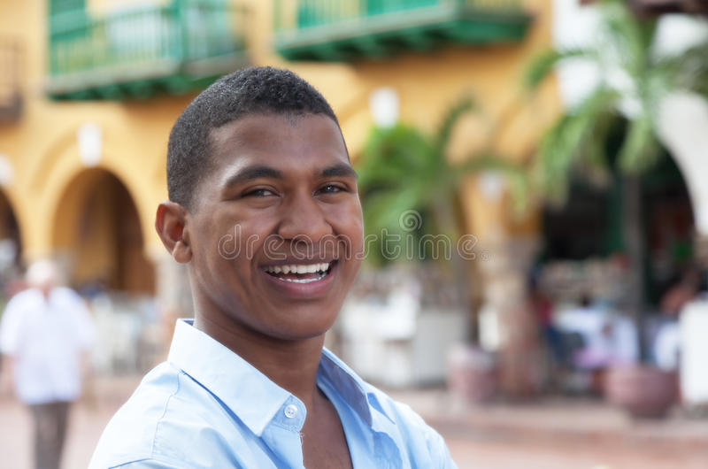 Laughing guy in a blue shirt in a colorful colonial town royalty free stock photos