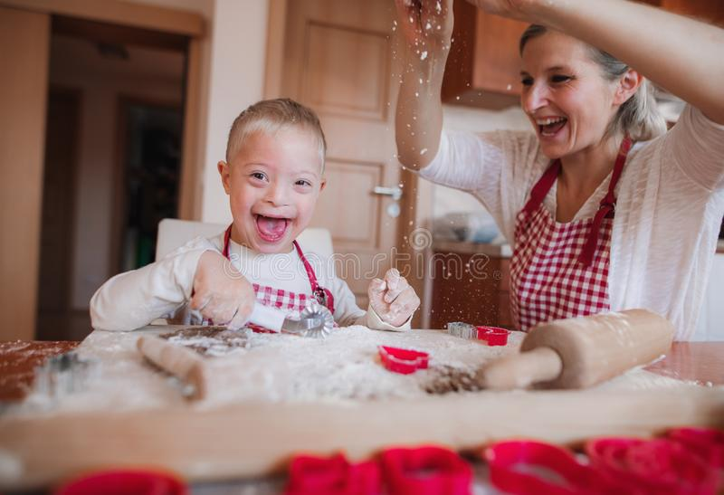 A laughing handicapped down syndrome child with his mother indoors baking. A laughing handicapped down syndrome child and his mother with checked aprons indoors royalty free stock image