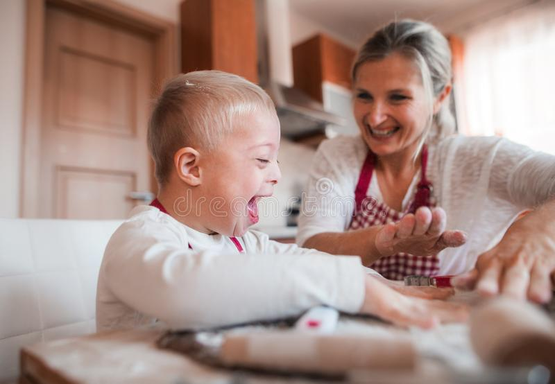 A laughing handicapped down syndrome child with his mother indoors baking. A laughing handicapped down syndrome child and his mother with checked aprons indoors royalty free stock photography