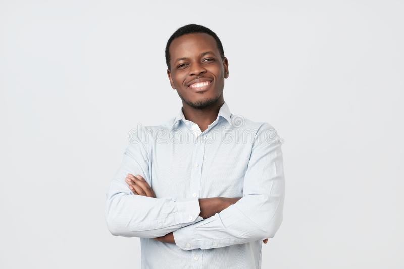 Laughing handsome young african man in shirt smiling confident stock photography