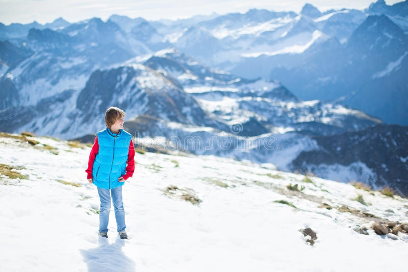 Laughing Happy Boy In Snow On Top Of Mountain Stock Photo