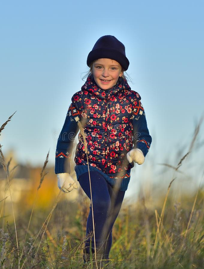 Laughing Happy little girl running on autumn meadow. stock photo