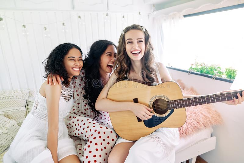Laughing happy women with guitar have fun together inside the camper van enjoy party. Different ethnics women friendship and females beauty concept stock images