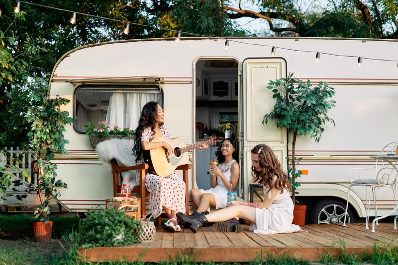 Laughing happy women with guitar have fun together outdoors near their camper van during summer travel stock photos