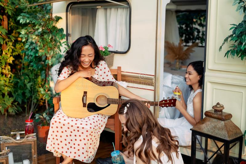 Laughing happy women with guitar have fun together outdoors near their camper van during summer travel stock photography