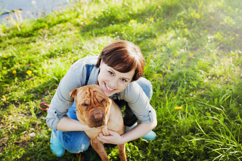 Laughing happy young woman in denim overalls hugging her red cute dog Shar Pei in the green grass in sunny day, true friends stock image