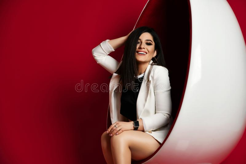 High-society woman brunette in white stylish jacket and black shirt sits poses in a modern oval chair and laughs on red stock photography