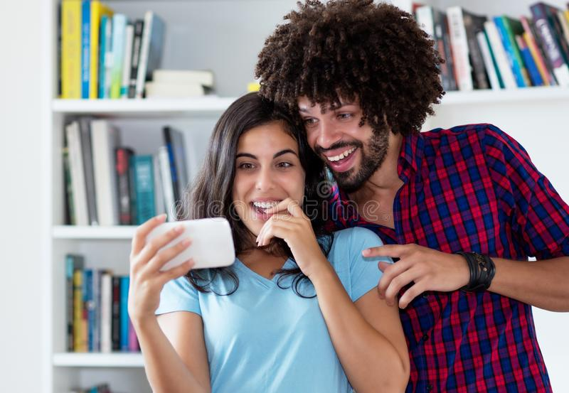 Laughing hipster love couple streaming clips with phone royalty free stock photo