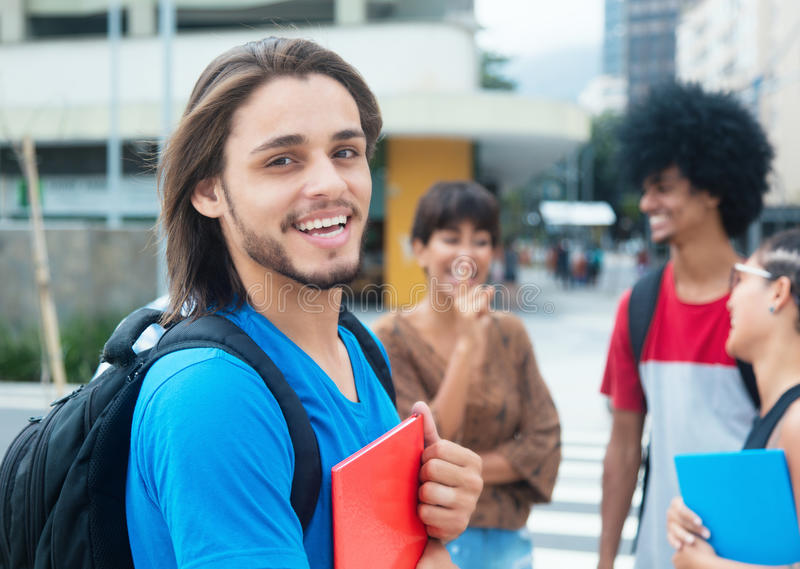 Laughing hipster male student with group of multi ethnic young a. Dults in city stock image
