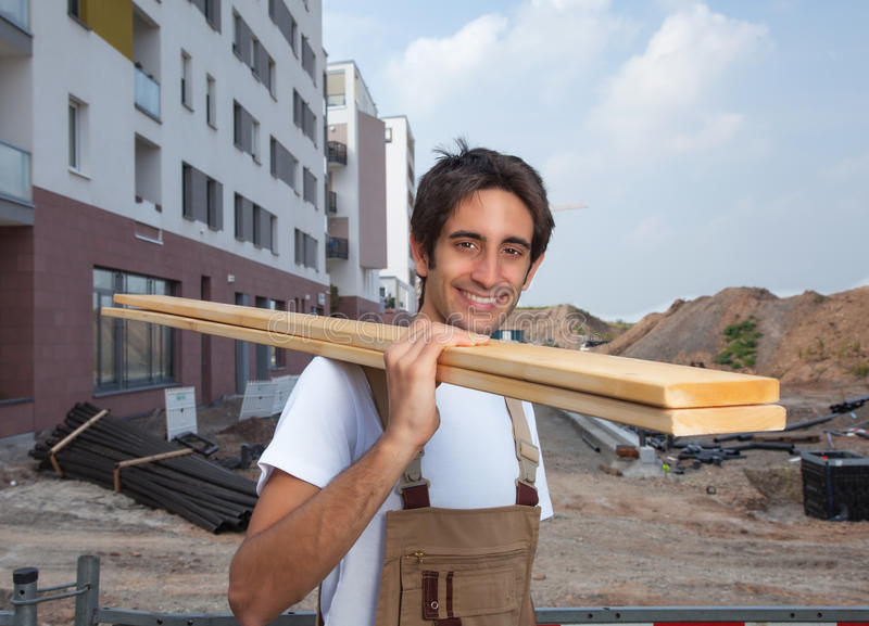 Laughing hispanic carpenter on construction site stock photography