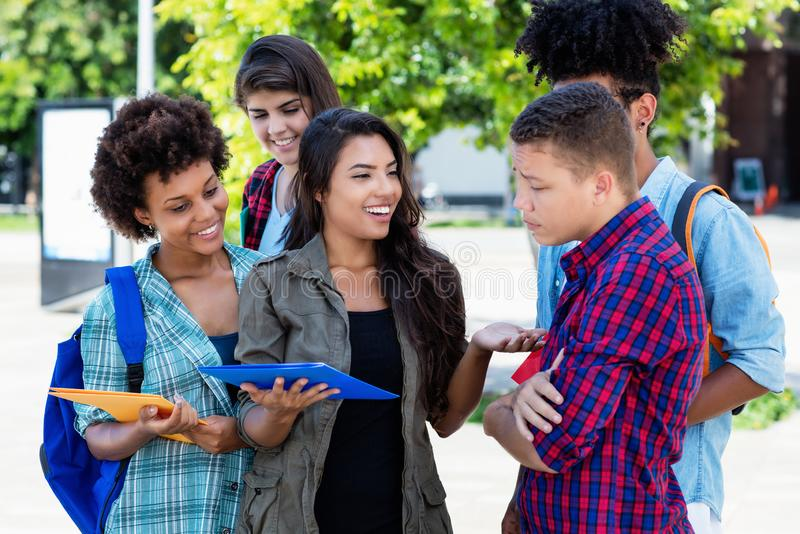 Laughing hispanic female student learning with group of latin and african american young adults. Outdoor at campus of university royalty free stock photo