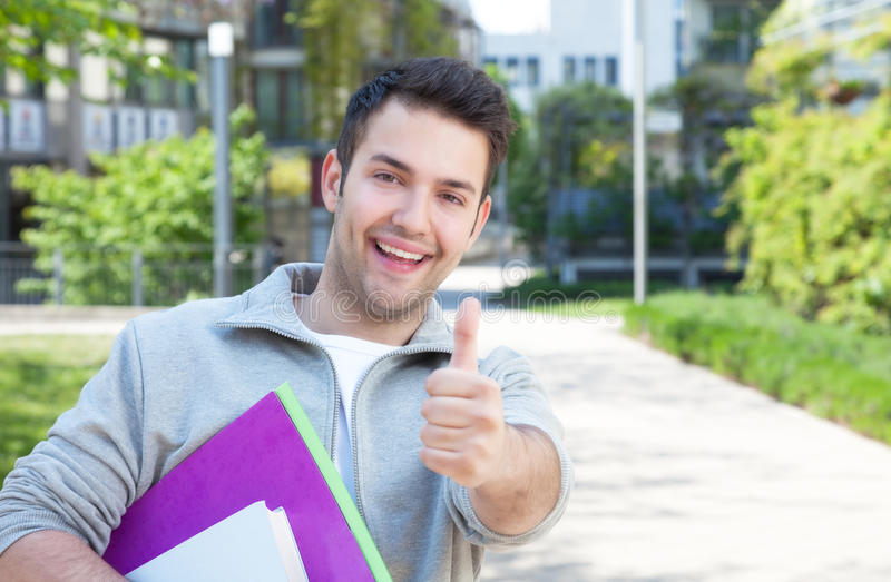 Laughing hispanic student at campus showing thumb up royalty free stock photography