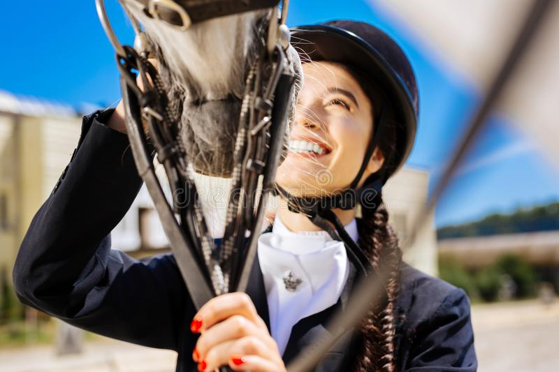 Laughing horsewoman with red nails touching her white horse royalty free stock image