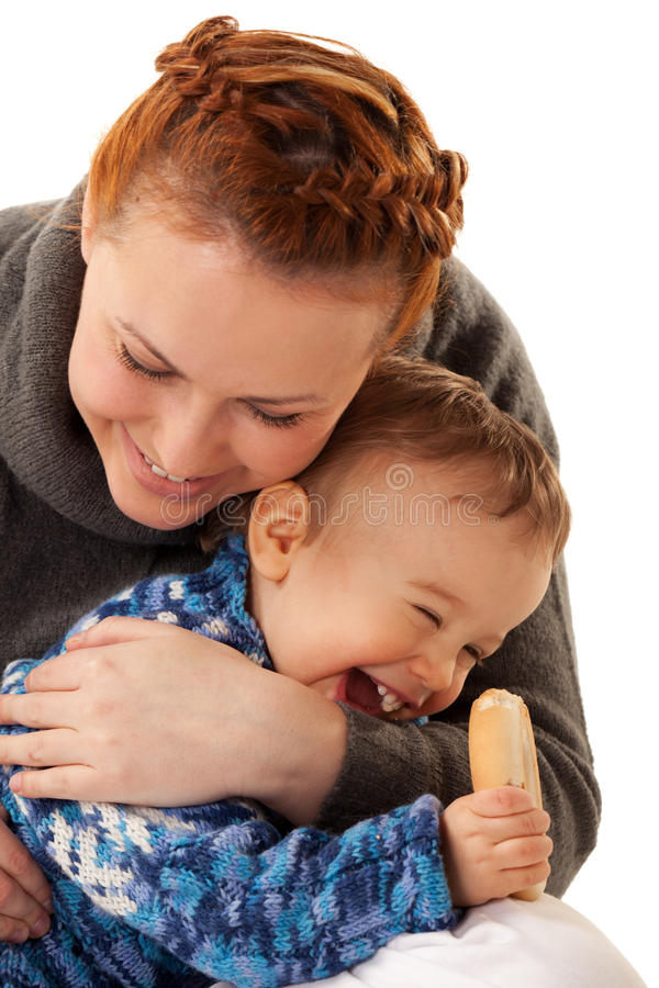 Laughing hungry boy. Laughing boy is nibbling dry biscuit sitting on mother's knees stock photography