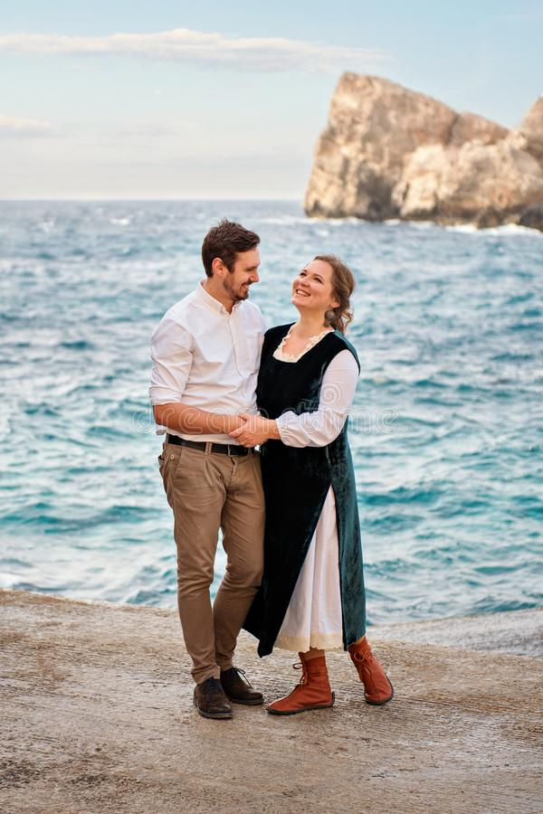 Laughing joyfully smiling family couple stands gently hugging with blue sea background and rocks in retro vintage clothers. Laughing joyfully smiling family royalty free stock image