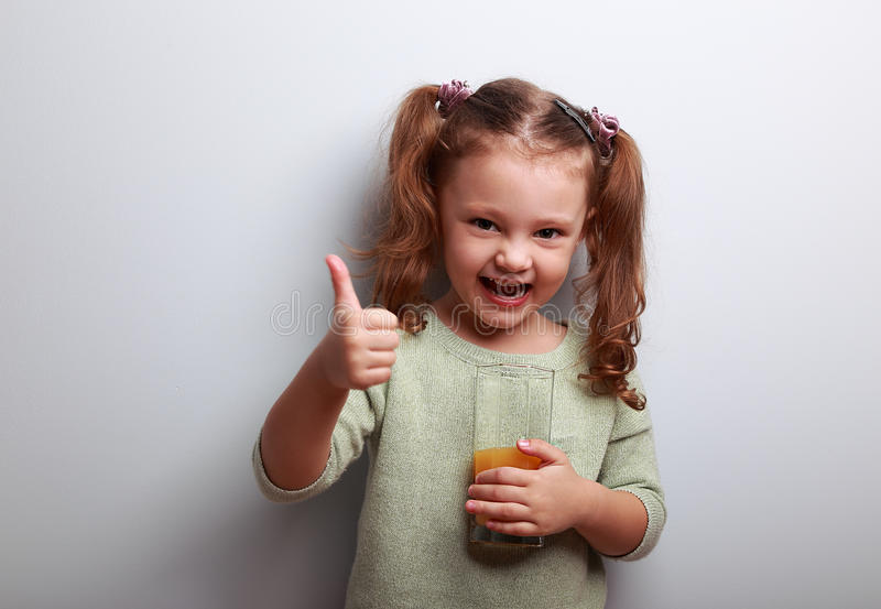 Laughing kid girl drinking juice and showing thumbs up sign royalty free stock photo