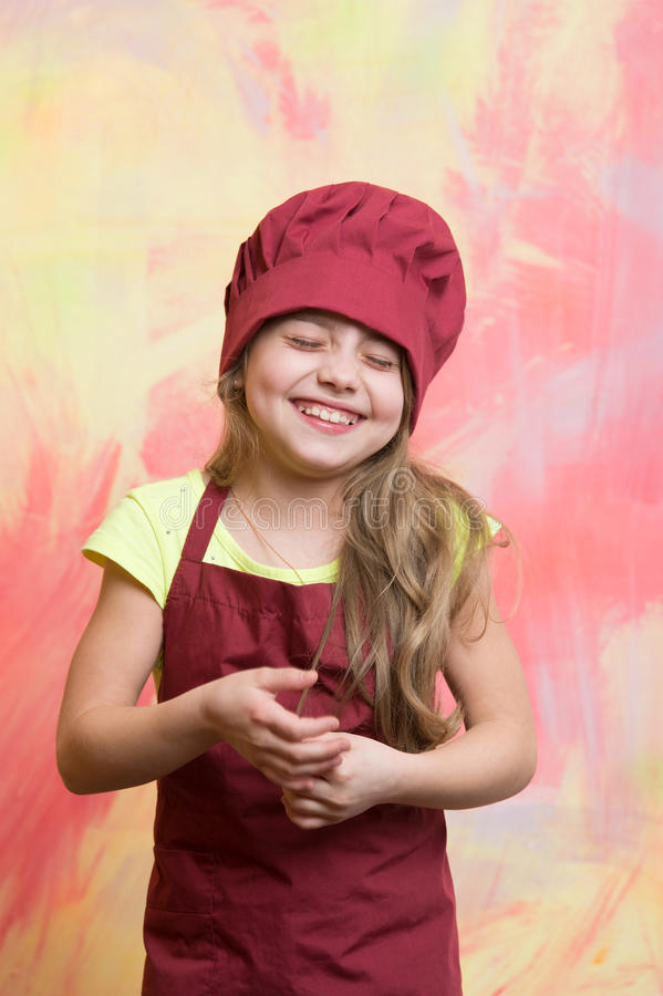 Laughing kid, happy girl cook in red chef hat, apron. Laughing kid or happy little girl cook in red chef hat and apron on colorful abstract background, cooking royalty free stock images