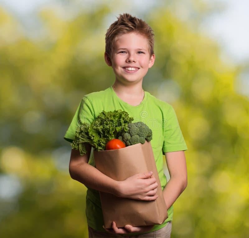 Laughing kid holding paper shopping bag full of fresh organic fr royalty free stock images
