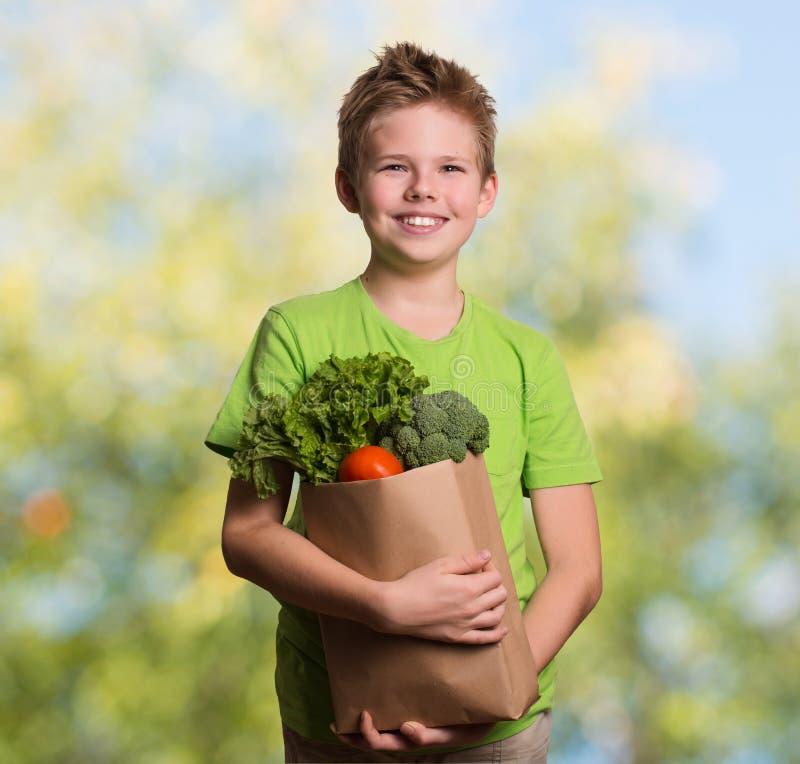Laughing kid holding paper shopping bag full of fresh organic fr royalty free stock photography