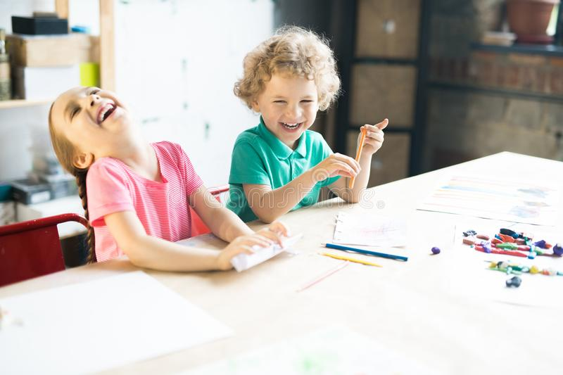 Laughing Kids Drawing at Table stock photo